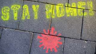 """A graffiti consisting of the text """"Stay Home"""" and a symbolic novel coronavirus has been sprayed on the ground in Munich, Germany, Monday March, 16, 2020. Berlin has closed all Bars and pubs because of the corona virus outbreak in Germany. For some, especially older adults and people with existing health problems, it can cause more severe illness, including pneumonia. (Sven Hoppe/dpa via AP)"""