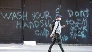 "A man wearing a protective face mask walks past a spray painted wall saying ""Wash your hands and don't touch your face"" Wednesday, March 18, 2020, in in downtown Vancouver, British Columbia. (Jonathan Hayward/The Canadian Press via AP)"