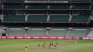Players from Richmond and Carlton play their Australian Rules Football league game at an empty Melbourne Cricket Ground in Melbourne on Thursday. Photo: Michael Dodge/AP