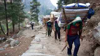 Porters with supplies for trekkers head towards Namche, in Zamphute, a village in Nepal.