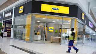 FILE PHOTO: A worker walks past an MTN store in Johannesburg