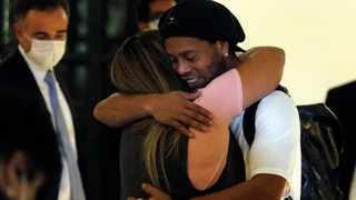 Former Brazilian soccer star Ronaldinho is embraced by a woman as he arrives at a hotel where he is to stay under house arrest in Asuncion, Paraguay. Picture: Jorge Saenz/AP