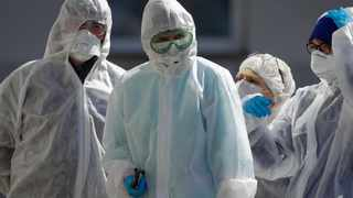 Belarusian healthcare workers wearing face masks and costumes to protect from coronavirus stand outside a hospital in Minsk, Belarus, Tuesday, April 14, 2020.  The highly contagious COVID-19 coronavirus pandemic is known to be a greater threat to the health of older people.(AP Photo/Sergei Grits)
