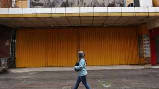 In this Thursday, April 30, 2020, photo, a woman walks past a shop closed due to the new coronavirus outbreak at Pasar Baru Shopping Center that is popular for its textiles products in Jakarta, Indonesia. May Day usually brings both protest rallies and celebrations rallies marking international Labor Day. This year it's a bitter reminder of how much has been lost for the millions left idle or thrown out of work due to the coronavirus pandemic. Garment workers in Asia are among the hardest hit as orders dry up and shutdowns leave factories shuttered. (AP Photo/Tatan Syuflana)