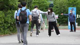 A senior student is greeted by a teacher, second from right, upon his arrival at the Kyungbock High School in Seoul, South Korea. South Korean high schools reopened on Wednesday after weeks of postponement due to safety concerns over the coronavirus outbreak. Picture: Ahn Young-joon/AP