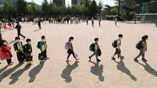 Pupils wearing face masks as a precaution against the new coronavirus, walk to their classrooms while maintaining social distancing after they attend the entrance ceremony at Chungwoon elementary school in Seoul, South Korea. Picture: AP