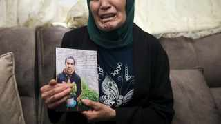 Rana, mother of Iyad Halak, 32, holds his photo at their home in East Jerusalem's Wadi Joz. Picture: AP