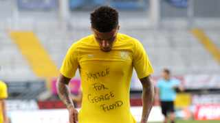Jadon Sancho of Borussia Dortmund celebrates scoring his teams second goal of the game with a 'Justice for George Floyd' shirt during the German Bundesliga soccer match between SC Paderborn 07 and Borussia Dortmund. Photo: Lars Baron/Pool via AP