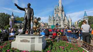 Guests watch a show near a statue of Walt Disney and Micky Mouse in front of the Cinderella Castle at the Magic Kingdom at Walt Disney World in Lake Buena Vista, part of the Orlando area in January. Picture: AP Photo/John Raoux.