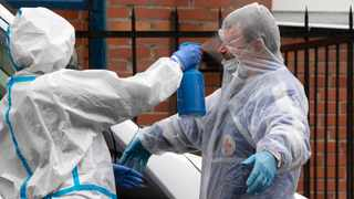 A medical worker wearing gear to protect against the coronavirus disinfects an ambulance driver in St Petersburg, Russia. Picture: AP Photo/Dmitri Lovetsky