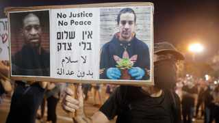 A protester holds a portrait of Eyad Hallaq, on the right, a Palestinian with severe autism who was killed recently by Israeli border police officers, and George Floyd who was killed during a police arrest in Minneapolis, Minnesota. Picture: Sebastian Scheiner/AP