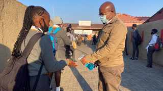 A staff member sanitizes the hands of students as schools begin to reopen after the coronavirus disease (COVID-19) lockdown in Soweto