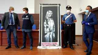 Italian authorities unveil a stolen artwork painted by the British artist Banksy as a tribute to the victims of the 2015 terror attacks at the Bataclan music hall in Paris,  during a press conference in L' Aquila. Picture: Andrea Rosa/AP