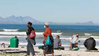 Women walk on the beach at Muizenberg, Cape Town, South Africa, Tuesday June 16, 2020. The country now has more than a quarter of the coronavirus cases on the 54-nation African continent with more than 73,000 cases after new, record-high infections were registered in South Africa over the weekend. (AP Photo/Nardus Engelbrecht)