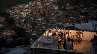 """Members of the """"Tempero de Criola"""" band perform in the Turano favela, in Rio de Janeiro, Brazil. A group of musicians playing Samba offered a small concert to the residents of Turano favela, most of whom remain quarantined to curb the spread of Covid-19. Residents could watch the performance from their windows, balconies or via internet. Picture: Silvia Izquierdo/AP"""