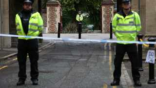 Police stand guard at the Abbey gateway of Forbury Gardens park in Reading town centre following Saturday's stabbing attack. Picture: Jonathan Brady/PA via AP