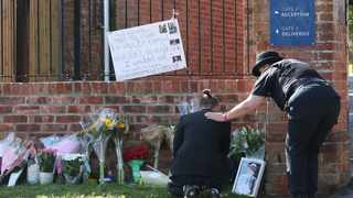 A mourner is comforted by a police officer as flower tributes are placed at the entrance to Holt School in Wokingham, England, in memory of teacher James Furlong, a victim of a terror attack in nearby Reading. Picture: Steve Parsons/PA via AP