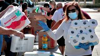 Volunteers prepare donations for delivery to those affected by Covid-19 on tribal lands in Tempe, Arizona, on Thursday. Picture: AP Photo/Matt York