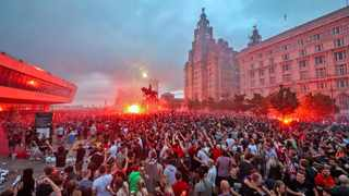 Liverpool fans let off flares outside the Liver Building in Liverpool on Friday, June 26, 2020, as celebrate their team winning the English Premier League title. Photo: Peter Byrne/AP