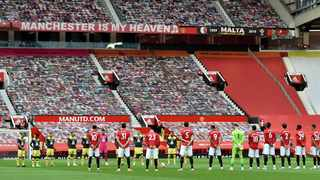 Players observe a minutes silence ahead of he English Premier League soccer match between Manchester United and Southampton at Old Trafford in Manchester, England on Monday, July 13, 2020. Photo: AP Photo/Peter Powell