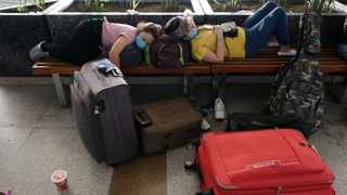Travellers rest on benches at Delhi Airport on May 25. Picture: Bloomberg photo by T. Narayan.