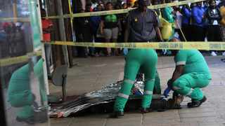 Paramedics and police cover the body of a man who died when he was chased by unknown men who stabbed him to death on Anton Lembede street in thr Durban CBD Picture: Doctor Ngcobo/African News Agency (ANA)