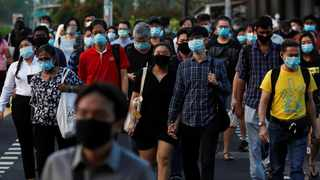 People cross a street during morning peak hour commute amid the coronavirus disease (Covid-19) outbreak in Singapore.  File picture: Reuters/Edgar Su