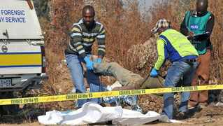 In this file picture, police remove the body of one of the alleged illegal miners killed in Benoni after violence between rival groups erupted. Picture: Antoine de Ras