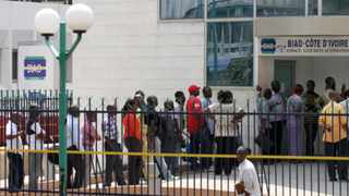 Customers queue to withdraw money outside a bank in Abidjan, as an exodus of foreign banks from the Ivory Coast turned a political crisis into financial meltdown.