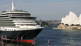Pedestrians walk next to the Queen Victoria cruise liner, docked at the Circular Quay, in central Sydney