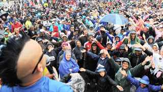 A crowd of participants and their families dance along with GoodHope FM's Carl Wastie while being showered by light rain during the entertainment period as walkers completed their trek. Photo: Michael Walker