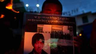 An exile Tibetan Buddhist monk carries a portrait of Lobsang Tsultrim, who self-immolated in Tibet during a candle lit vigil to remember Tibetans who have self-immolated since March 2010, in Dharmsala, India.