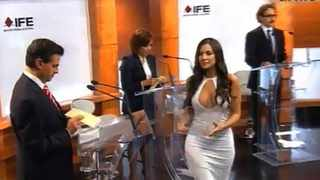 In this screenshot taken from Mexico's Federal Electoral Institute's YouTube channel, Julia Orayen (second from right) carries a box to presidential candidates so they can choose their speaking order during a debate in Mexico City on May 6. The Federal Election Commission, which organised the event, said an independent producer had hired the former Playboy model, and acknowledged that her revealing attire was a mistake.