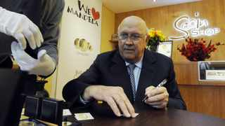 Cape Town. 120514. FW De Klerk signs some gold coins with his face on them which will be sold at a special price. FW De Klerk and Alan Demby opened the 30th Scoin Shop at the Victoria and Alfred Waterfront today. Reporter Xolani. Picture Courtney Africa