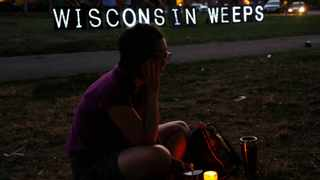 File photo - A woman sits with a candle during a vigil for the victims of the Sikh Temple of Wisconsin shooting, in Milwaukee.