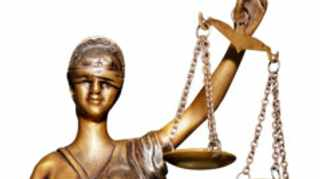 Statue of justice holding balanced scales in hand isolated on white background