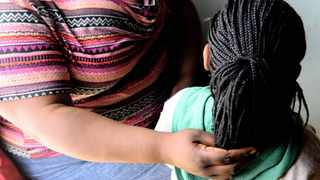 The two year old girl who was raped by her HIV positive father is being cuddled by her mother at their home in Soweto. 240413 Picture: Boxer Nqobizwe Ngwenya