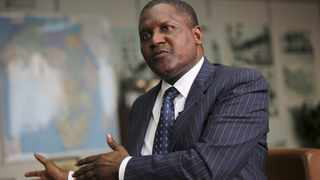 Nigerian billionaire Aliko Dangote gestures during an interview with Reuters in his office in Lagos June 13, 2012. Dangote is targeting a market capitalisation of $35-40 billion for his cement company when he lists it in London next year, and the money will be used to pay off investors including himself, he told Reuters on Wednesday. Africa's richest man with a cement empire stretching from Senegal to South Africa, Dangote said in an interview at his office in Lagos that Dangote Cement had raised its capacity target to 60 million tonnes a year by 2015 from a previous 50 million tonne target. To match Interview NIGERIA-DANGOTE/      REUTERS/Akintunde Akinleye (NIGERIA - Tags: PROFILE SOCIETY WEALTH BUSINESS)