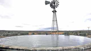 Storm clouds loom over a borehole windmill near Carnavon in South Africa's remote and arid Northern Cape province in this picture taken May 17, 2012. Carnavon is the proposed South African site for the Square Kilometre Array (SKA) telescope. South Africa is bidding against Australia to host the SKA, which will be the world's largest radio telescope when completed. Picture taken May 17, 2012.   REUTERS/Mike Hutchings (SOUTH AFRICA - Tags: SCIENCE TECHNOLOGY)