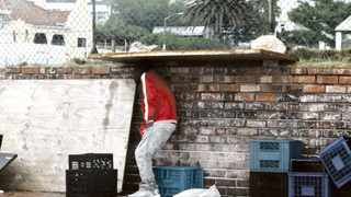 Cape Town - 131114 - A man shelters underneath a door on the Camps Bay strip. Another windy and rainy day in Cape Town. PICTURE: THOMAS HOLDER.