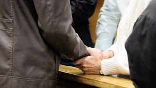 Family members of the Steenkamp's hold the hand of the murder- accused. Photo: Danie Van der Lith