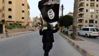 A supporter of the Islamic State in Iraq and the Levant group waves an ISIL flag in Raqqa.