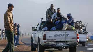 A bakkie moves off after loading unemployed builders and painters from a roadside for work in Cape Town. Picture: EPA/NIC BOTHMA