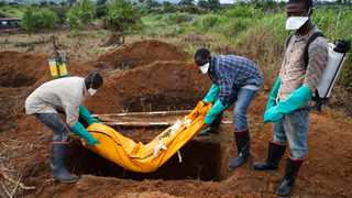 Volunteers in protective suit burry the body of a person who died from Ebola in Waterloo on October 7, 2014. Picture: Florian Plaucheur