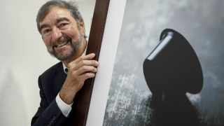 Nespresso inventor Eric Favre poses with a picture of a coffee capsule. Favre conceived of single-portion coffee pods four decades ago. Picture: Fabrice Coffrini
