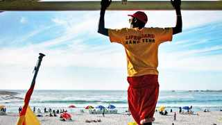 Cape Town - 111106 - Lifeguard, Lonwabo Ngqina, 20, watches over Camps Bay Beach on a warm summers day. Picture: Candice Chaplin