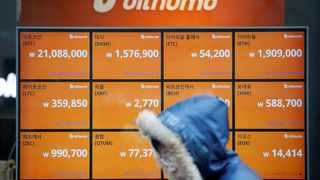 A man walks past an electric board showing exchange rates of various cryptocurrencies at Bithumb cryptocurrencies exchange in Seoul, South Korea, today.  Picture: Reuters