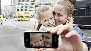 A mother and her daughter taking photos.