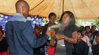 PROPHET OF DOOM: Lethebo Rabalago of Mount Zion General Assembly in Limpopo sprays insecticide on a congregant. Picture: Facebook