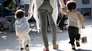 A woman walks with two toddlers in the patio of the Centro Madre Assunta, a shelter for migrant women and children, in Tijuana, Mexico, on June 20. Most of the women and children at the shelter had fled violence in southern Mexico and Central America and arrived in Tijuana with the intention of crossing the US-Mexico border to seek asylum in the US. The shelter, which is run by sisters of the Missionaries of San Carlos Borromeo, housed about 80 people.  Picture: David Maung/EPA-EFE